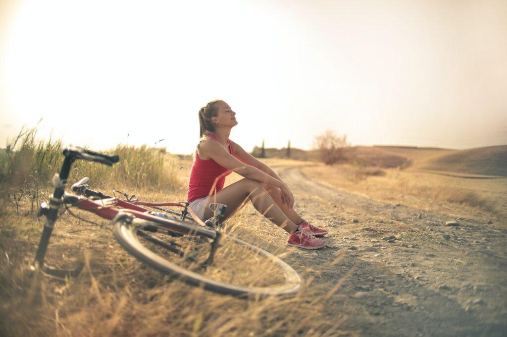 Treking kolesarka počiva na makadamu s poležanim kolesom in zaprtimi očmi.